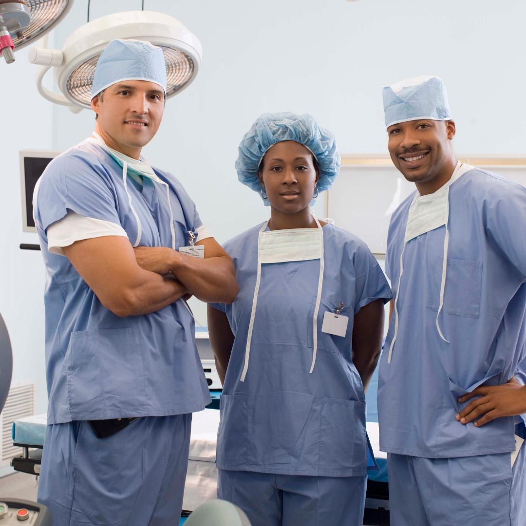 Three doctors or nurses standing around in scrubs.