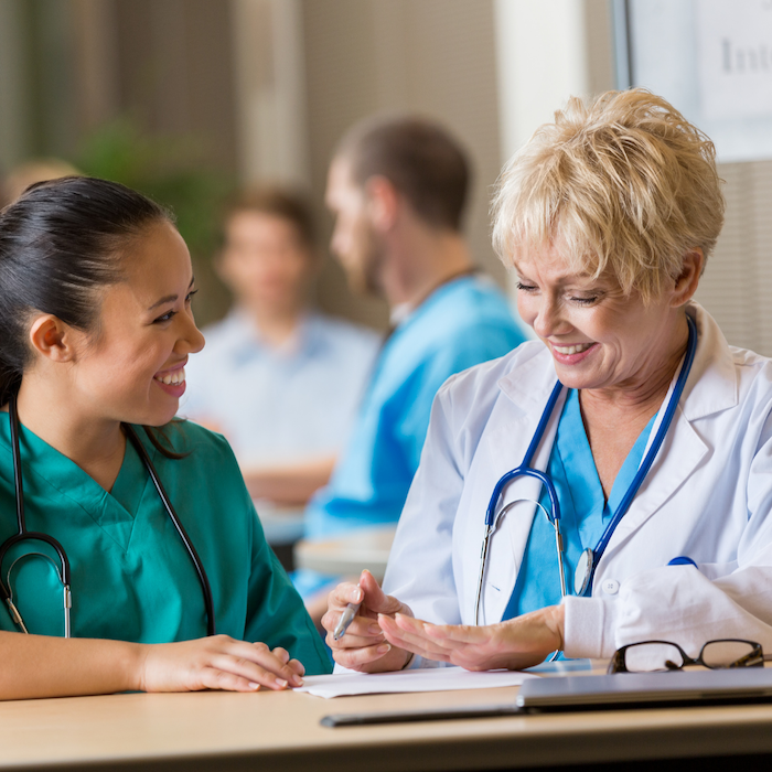A doctor happily chatting with a nurse