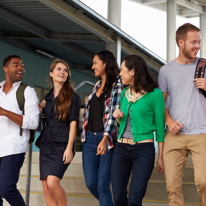 A group of five student walking down stairs conversing
