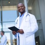 Portrait of smiling doctor standing with digital tablet
