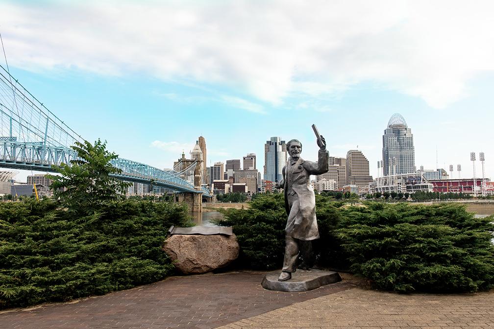 A statue with the skyline of Cincinnati as a backdrop